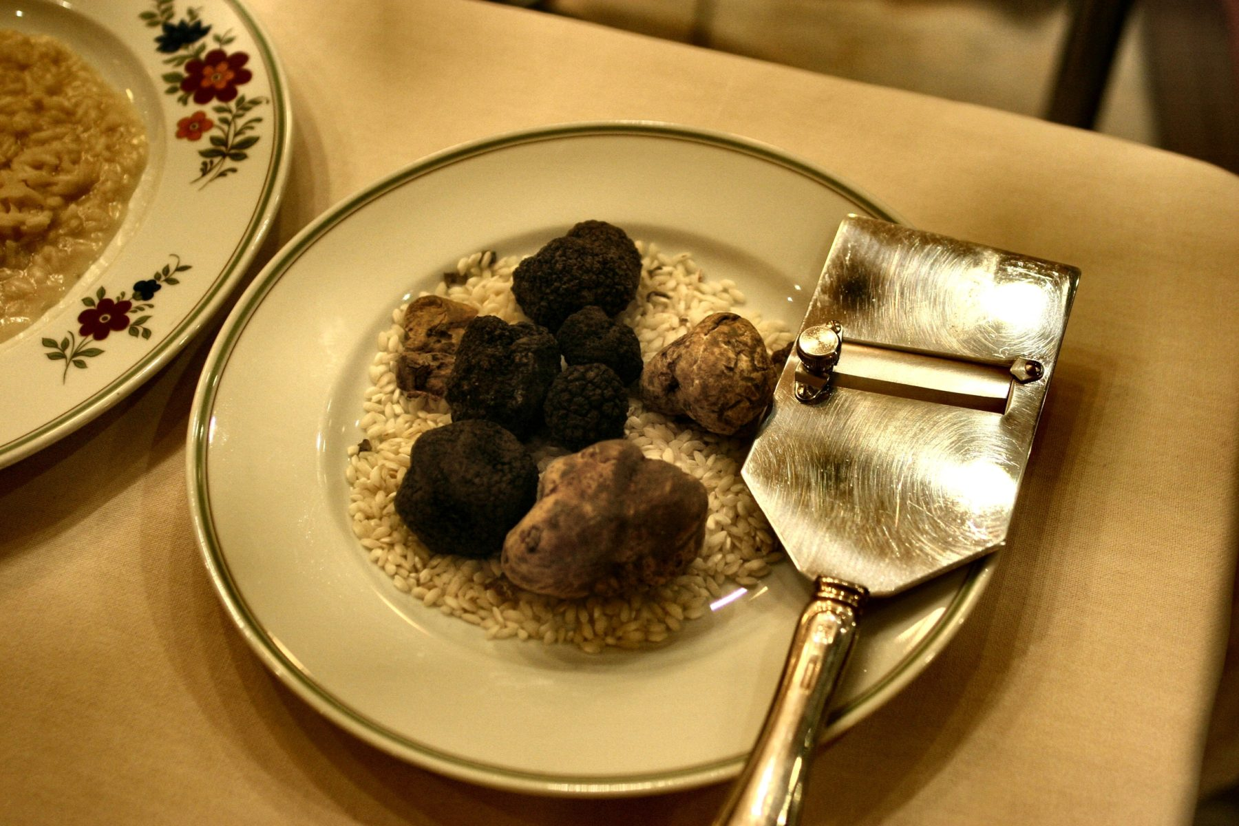 Truffles on a plate next to a metal truffle slicer