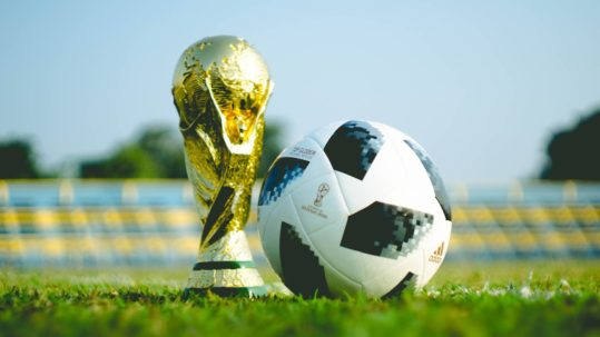 2018 FIFA World Cup trophy next to soccer ball